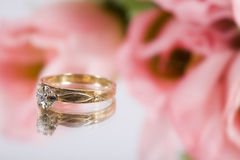 Engagement Ring. A gold engagement ring with some pink flowers royalty free stock images