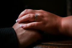 Engagement Ring. A couple holding hands displaying a diamond engagement ring Stock Photography