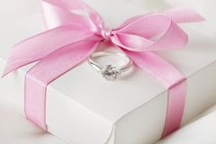 Engagement ring. Beautiful engagement ring and gift box with ribbon bow royalty free stock photo
