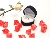 Engagement ring in black box. Close-up of an engagement ring in a heart-shaped box with a white rose and red crystals Stock Image