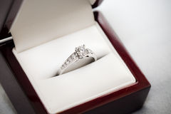 Engagement Ring in Box. Channel-set engagement diamond ring in an open red wood box royalty free stock photography