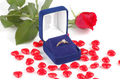 Engagement Ring In A Box. Diamond ring in a velvet bos with a red rose and candy hearts Royalty Free Stock Images