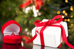 Engagement Ring in Box and Luxury present in red ribbon. Engagement Diamond ring in a red box and present royalty free stock photos