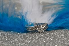 Engagement Ring and feathers. White Gold diamond engagement ring with blue and white feathers royalty free stock photos