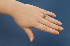 Engagement Ring Female Hand. Female hand over blue background wearing a diamond engagement ring with white gold body Royalty Free Stock Image