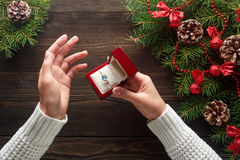 Engagement ring in female hands among Christmas decorations on wood background Stock Photo