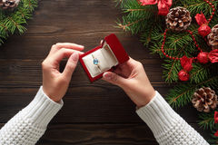 Engagement ring in female hands among Christmas decorations on wood background Royalty Free Stock Photography
