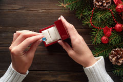Engagement ring in female hands among Christmas decorations on wood background Stock Photos