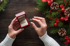 Engagement ring in female hands among Christmas decorations on wood background Royalty Free Stock Image