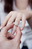 Engagement ring into a finger Stock Images