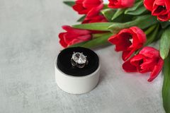 Engagement ring with giant diamond in a round white box on a sharpen grey background and with a bouquet of red tulips stock photo