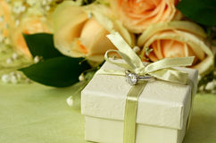 Engagement ring and gift box. On floral background royalty free stock photo