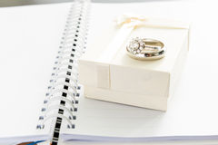 Engagement ring and gift box on note book Stock Photos