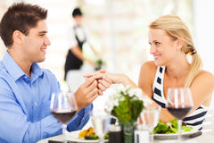 Engagement ring on girlfriend. Young men putting engagement ring on his girlfriend after she said yes stock image