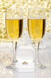 Engagement ring with glasses of champagne. Closeup of engagement ring with glasses of champagne Royalty Free Stock Photo