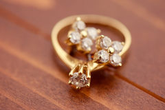 Engagement ring with golden earrings Stock Photos