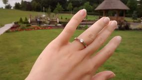 Engagement ring on a hand green grass background royalty free stock images