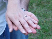 Engagement Ring. Hands of a newly engaged couple wearing white shirts and blue jeans Royalty Free Stock Image