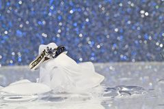 Engagement Ring on ice. White Gold diamond engagement ring on ice cubes against a silver and blue sparkle background royalty free stock photo