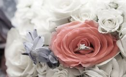 Engagement ring nesting in brides`s bouquet of flowers royalty free stock photos