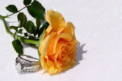 Engagement Ring. Next to a pretty rose on a sparkling white surface Stock Photo