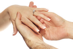Engagement Ring Placement. Male hands placing engagement diamond ring on brides hand Royalty Free Stock Images