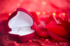 Engagement ring and red rose petals Royalty Free Stock Images
