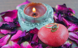 Engagement ring on the soap, rose petals, candles with flames Stock Photo