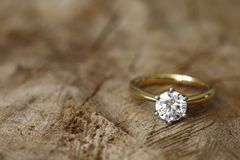 Engagement ring. Solitaire engagement diamond ring won wooden organic background stock photos