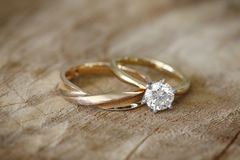 Engagement ring and wedding band. Solitaire engagement diamond ring with wedding band on wooden organic background Royalty Free Stock Photo