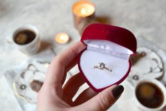 The engagement ring in woman`s hand. Romantic breakfast for a couple in love. Engagement ring in the box. The ring as a symbol of love Royalty Free Stock Photo