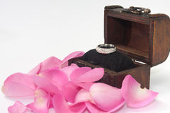 Engagement ring in the wooden chest with pink rose petals Royalty Free Stock Photo