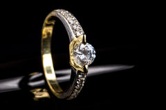 Engagement ring of yellow and white gold with sparkling diamond Stock Photos