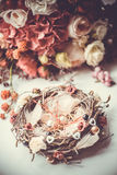 Engagement rings on nest-styled pillow. In front of bridal bouquet with red and burgundy flowers on white background royalty free stock photo