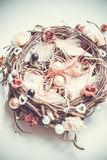 Engagement rings on nest-styled pillow. In front of bridal bouquet with red and burgundy flowers on white background stock photography