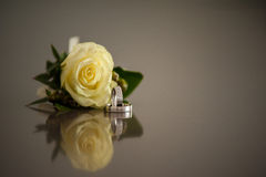 Engagement rings with yellow rose. And reflection on a marble table Stock Photography