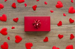 Engagement romantic arrangement concept with felt red hearts, and gift box on a wooden table. Copy space for text royalty free stock image