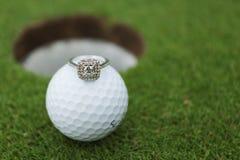 Engagement/Wedding ring alongside a golf ball. Engagement/Wedding ring on top of a golf ball Royalty Free Stock Image