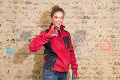 Engagierte Handwerkerin mit den Daumen oben vor Backsteinmauer in b stockfoto
