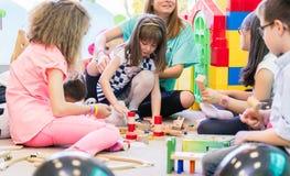 Engagierte Kindergärtnerin, die ein schüchternes Mädchen beim Aufpassen des Kinderspiels hält lizenzfreies stockbild