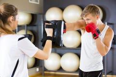 Engagierter Boxer-Sandsack gehalten vom Lehrer Stockfotografie