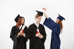 Enganar falador de sorriso de três graduados alegres guardando diplomas sobre o fundo branco Imagens de Stock Royalty Free