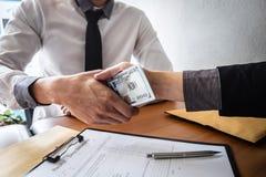 Engano desonesto no dinheiro ilegal do negócio, aperto de mão do homem de negócios com dinheiro de cédulas do dólar nas mãos de q fotografia de stock