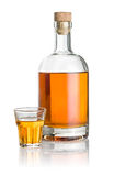 Engarrafe e vidro de tiro chanfrado enchido com o líquido ambarino Fotografia de Stock