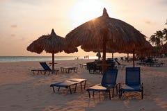 Engazonnez les parapluies à la plage sur Aruba au coucher du soleil Photographie stock libre de droits