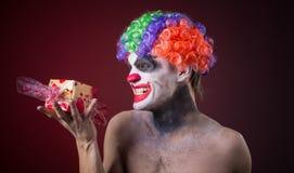 Enge clown met griezelige make-up en meer suikergoed Stock Fotografie