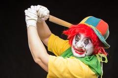 Enge clownjoker met een glimlach en rood haar met een groot mes  Stock Foto