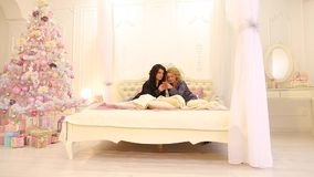 Enge Freunde benutzen modernes Gerät für Unterhaltung und sind gesellig und sitzen auf Bett im hellen Schlafzimmer auf Spätwinter stock video footage
