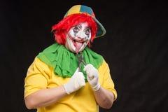 Enge kwade clown met een lelijke glimlach en een paar buigtang op bl Royalty-vrije Stock Afbeeldingen