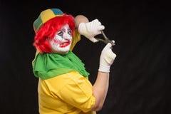 Enge kwade clown met een lelijke glimlach en een paar buigtang op bl Royalty-vrije Stock Fotografie